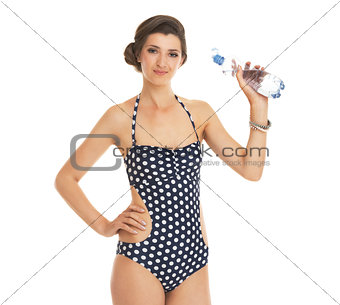 Portrait of young woman in swimsuit with bottle of water