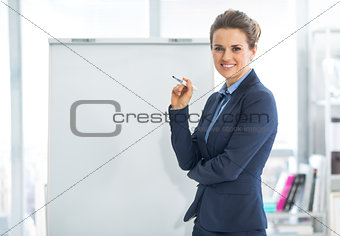 Portrait of happy business woman near flipchart