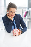 Portrait of thoughtful business woman with piggy bank