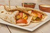 Burritos filled with chicken, peppers, rice and tomato
