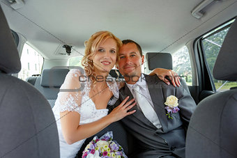 beautiful young wedding couple in car