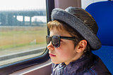 Handsome boy in sunglasses rides on a train