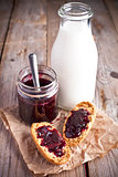 black currant jam in glass jar, milk and crackers