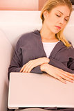 Young woman resting sofa while using laptop