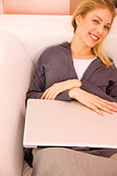 Smiling young woman with laptop lying couch