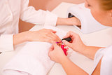 Beautician applying nail varnish to woman