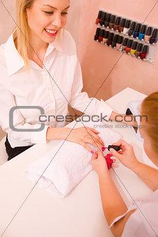 Beautician applying nail varnish to young woman