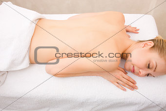 Topless young woman lying massage table