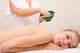 Woman lying massage table in front of masseuse