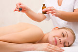 Therapist putting essential oil woman's back