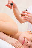 Masseuse pouring massage oil woman's back