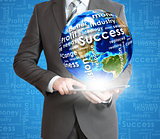 Businessman holds tablet pc with Earth in hand