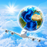 Earth with airplane against clouds and sun