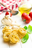 italian pasta tagliatelle, tomatoes and basil leaves