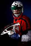 Lacrosse player wearing helmet and holding stick. Studio shoot on the black background with blue light spot.