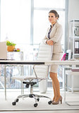 Full length portrait of thoughtful business woman standing in of