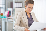 Happy business woman examining documents in office