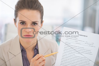 Portrait of business woman pointing on document