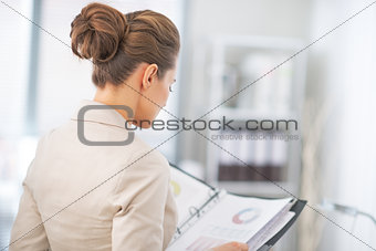 Business woman examining documents in office. rear view