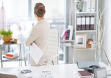 Business woman standing with document in office. rear view