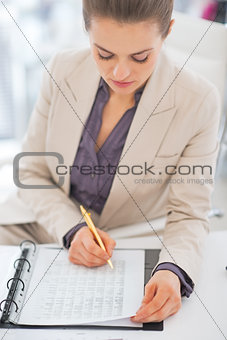 Portrait of business woman writing in document