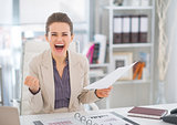 Happy business woman with document rejoicing