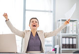Happy business woman with document rejoicing at work