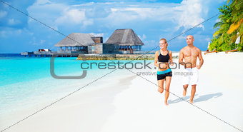 Happy couple jogging on the beach