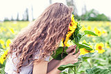 The girl smells sunflowers