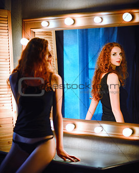 Portrait of beautiful young red-haired woman looking into mirror