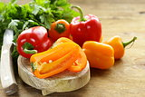 fresh colorful bell peppers on a wooden background