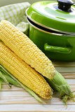 ripe yellow corn and green pan on a wooden background