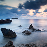 Stunning landscape dawn sunrise with rocky coastline and long exp
