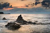 Stunning landscape dawn sunrise with rocky coastline and long ex