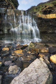 Beautiful landscape image waterfall flowing into rocks on beach