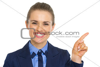 Portrait of smiling business woman pointing on copy space
