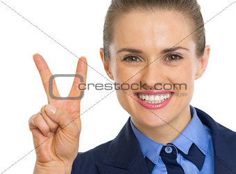 Smiling business woman showing victory gesture