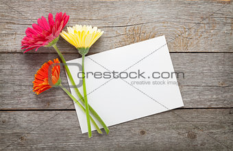 Three colorful gerbera flowers and blank greeting card