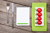 Fresh tomatoes, silverware and notepad for copy space