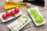 Tomatoes, mozzarella and green salad leaves with condiments