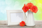 Orange gerbera flowers and photo frame