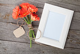 Bunch of gerbera flowers and photo frame