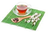 Japanese green tea and sakura branch over bamboo mat