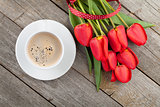 Fresh red tulips with ribbon and coffee cup