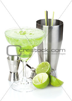 Classic margarita cocktail with salty rim, limes and drink utens