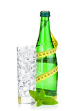 Glass of water with ice, bottle, measuring tape and mint
