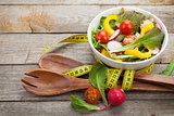 Fresh healthy salad, utensil and measure tape