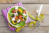 Fresh healthy salad, silverware and measure tape