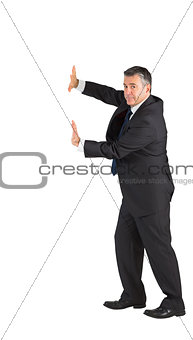 Mature businessman pushing with hands