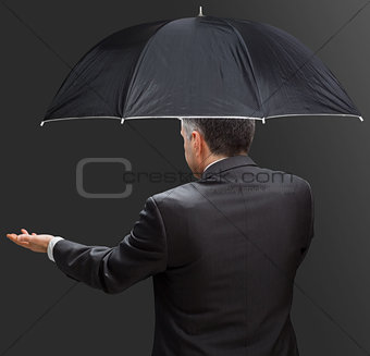 Businessman holding umbrella and reaching hand out
